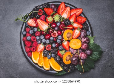 Fruits and berries in plate copy space.