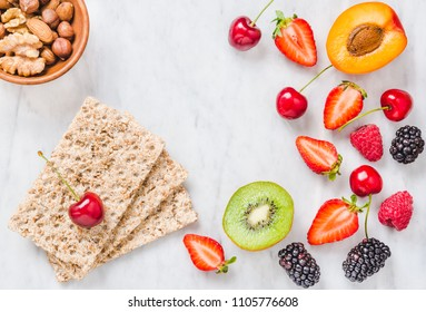 Fruits, berries and whole grain crisp bread toast on white marble table copy space.The concept of diet and breakfast healthy eating.