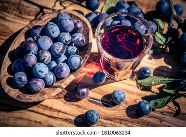 fruits of the blackthorn bush and a glas on olive wood - Shutterstock ID 1810063234