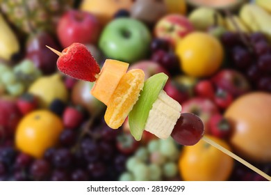 Fruits brochette with a blurred fruits background. It has a clipping path.