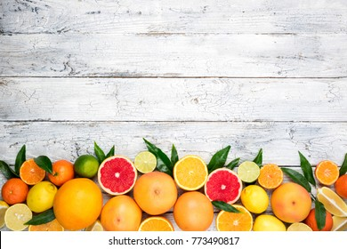 Fruits citrus background. Orange, grapefruit, lemon, lime, tangerine. Assorted fresh fruits with leaves. Top view, flat lay. Copy space