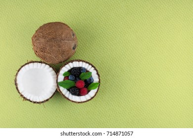 Fruits of coconuts on green background with mix of berries. Colorful diet and healthy eating concept. Flat lay style.