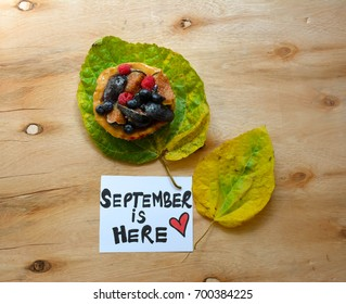 A fruits cookie over autumn leaves and September is here text on a note on wooden table