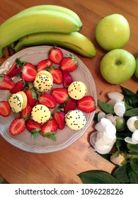 Fruits and flowers with sweet french macarons, dark wooden table. Top view.
