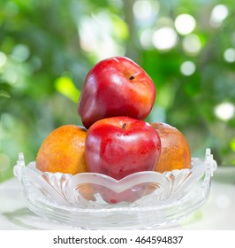 Fruits in the glass basket on tile plate / selective focus