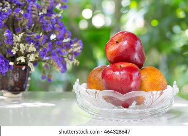 Fruits in the glass basket and vase flower on tile plate / selective focus