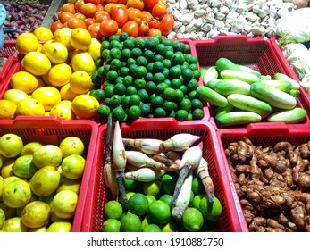 fruits and herbs that are sold in the market, consisting of lemon, lime, tomato, cucumber, galangal, garlic, shallot and cabbage.