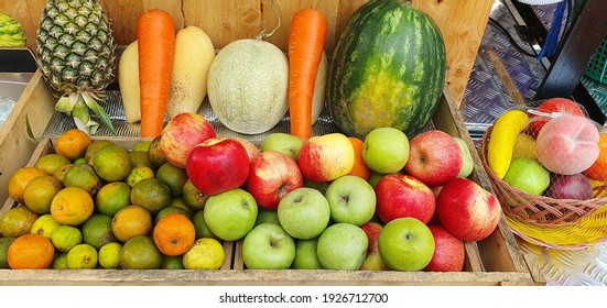 Fruits in a juice shop include oranges, green and red apples, carrots, watermelon, cantaloupe, mango, and lime. And pineapple prepared for customers to choose to make a fruit smoothie