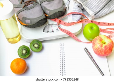Fruits and notebook note changes in weight loss.