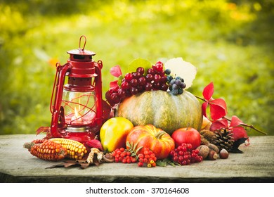 Fruits and nuts, pumpkins on the table outdoor and kerosene lamp - cozy autumn