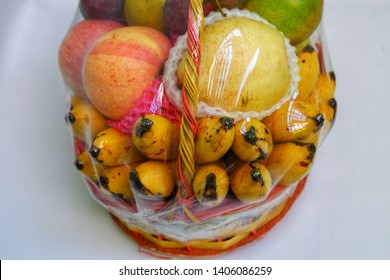 Fruits parcel (banana,grape,orange,apple,guava,pear) on the woven basket isolated on white background. Top view close up details.