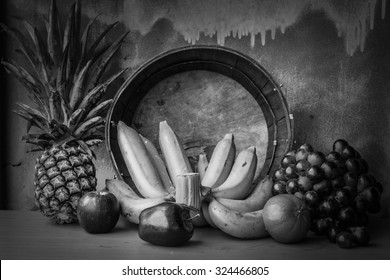 fruits placed on wooden tables laid with black and white images.