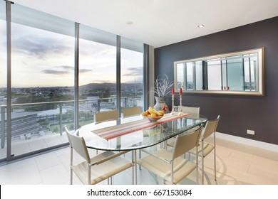 Platos de frutas sobre mesa, muebles y diseños cómodos, paredes de color blanco, sillas alrededor de las mesas, dentro de las habitaciones de un apartamento.