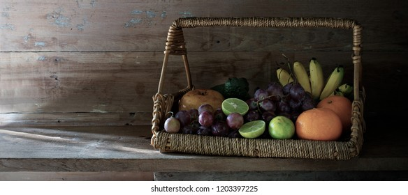 Fruits in the rattan basket on old plank and old wooden wall / Still life image and select focus, adjurtment, size, color, for banner, cover, header, backgronnd