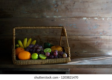Fruits in the rattan basket on old plank and old wooden wall / Still life image and select focus
