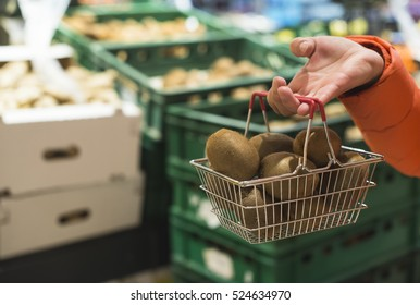 Fruits in supermarket. Buying kiwi in shop. Small basket.