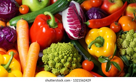 Fruits and vegetables fresh organic and assorted variety scattered on a table close up top view background.