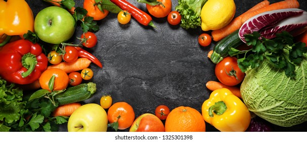 Fruits and vegetables fresh organic and assorted variety scattered on a table forming a frame with copy space top view background.