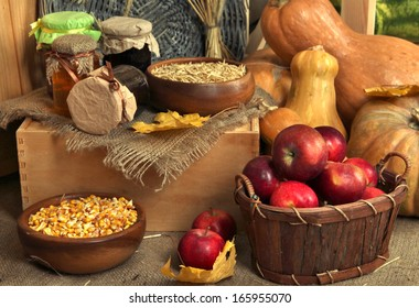 Fruits and vegetables with jars of jam and bowls of grains on sackcloth on wooden background