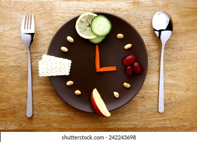 fruits, vegetables, nuts and crackers arranged on a plate like a clock