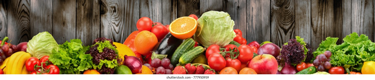 Fruits and vegetables on background of wooden wall. Healthy vegetarian food. Copy space