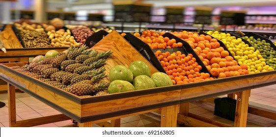 Fruits and vegetables on display in a supermarket. Food store. Pineapple, melon, grapefruit, tangerine, orange, lemon. Organic food. Beautiful image.