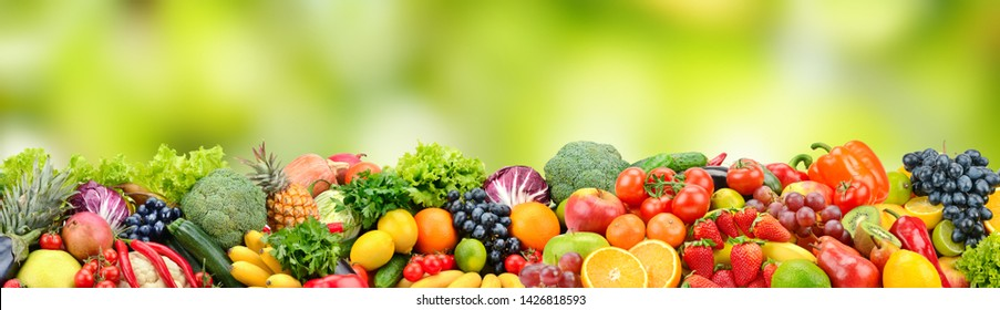 Fruits and vegetables on green blurred background. Wide panorama with free space for text.