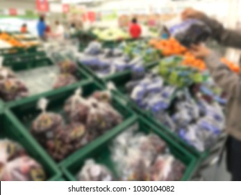 Fruits and vegetables on shelves in supermarket blur background.Blurred supermarket, grocery with customers shopping, bokeh light background. Healthy concept.