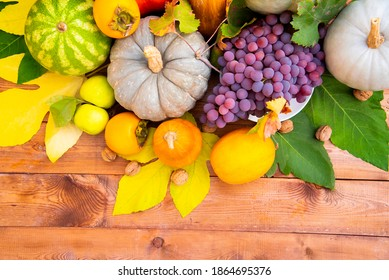 Fruits and vegetables, pumpkin, watermelon, yellow melon; persimmon, Apple; walnut; grapes, and colorful leaves are appetizing on a wooden background on a Sunny day. The Gifts Of Autumn
