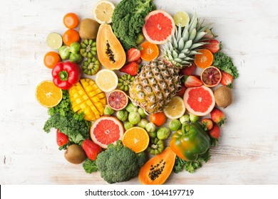 Fruits and vegetables rich in vitamin C background circle shape, oranges mango grapefruit kiwi kale pepper pineapple lemon sprouts papaya broccoli, on white table, top view, selective focus
