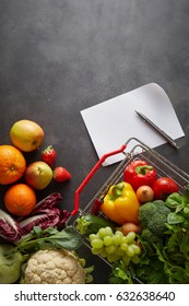 Fruits and vegetables in shopping basket and on table, near blank white shopping list and pen and copy space over clean blackboard background