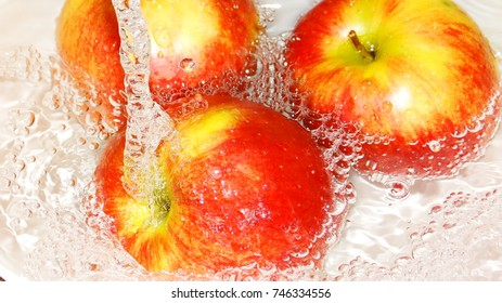 Fruits in water in a white porcelain dish.