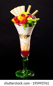 Fruits with whipped cream on a black background isolated