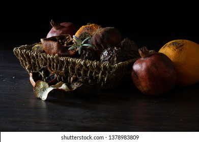 Fruits withered dried and rotten in rattan basket on dark background / Select focus and space for texts, still life
