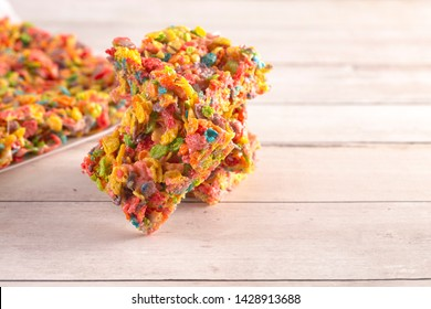 Fruity Cereal Marshmallow Treat Bars on a Light Wood Table