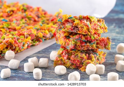 Fruity Cereal Marshmallow Treat Bars on a Blue Wooden Table