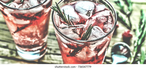 Fruity cocktail drink decorated with frozen or fresh raspberry, strawberry, rosemary, ice and soda. Domestic cocktail with ice and rosemary