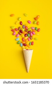 Fruity jellybeans. Tasty colorful jelly beans and waffle cone on yellow background. Top view.