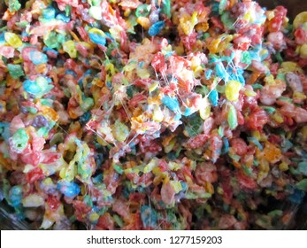 Fruity Pebbles cereal being mixed with marshmallow to create the final treat