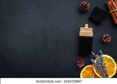 Fruity perfume for women. Bottle of perfume near orange, lavender, cinnamon on black background top view copy space border