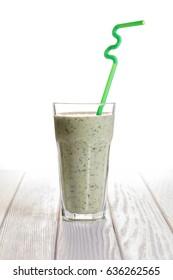 Fruity spinach milkshake on a white wooden background
