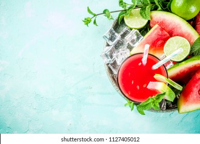 Fruity summer cold drink, homemade watermelon juice or smoothie served with lime and fresh mint leaves, light blue trendy background copy space top view