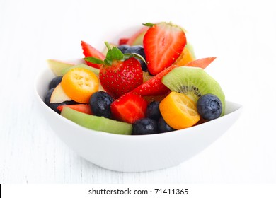 Fruity summer salad in white bowl on white background