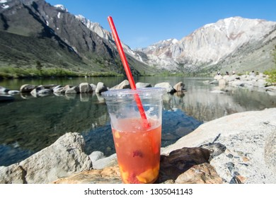 Fruity tea drink placed in front of Convict Lake located off of US-395, near Mammoth Lakes California in the eastern Sierra Nevada mountains,