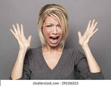 frustrated 20s blond girl crying, losing temper, screaming loud with hands up