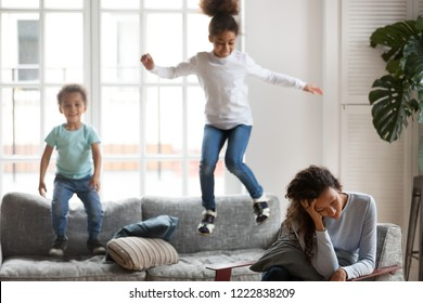 Frustrated African American woman having problem with children upbringing, upset single mother hold head in hands, playful son and daughter jump on couch, depression, difficulties with educate kids