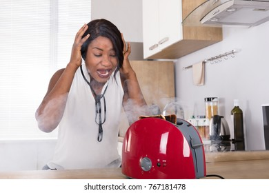Frustrated African Young Woman Looking At Burnt Toast Coming Out Of Toaster In Kitchen