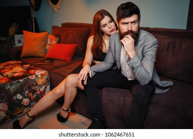 Frustrated angry bearded man sitting on couch turned back ignoring wife, problems in relationships, married couple having quarrel at home, unhappy husband and wife arguing, bad relationships concept