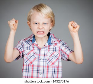 A frustrated and angry looking young boy with fists clenched and pulling a face. Isolated on white.