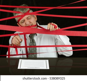 Frustrated angry man caught in political bureaucratic red tape regulations as he struggles to reach the contract in front of him awaiting his signature so he can move forward with successful business